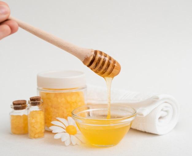 Gros plan personne avec du miel et des sels