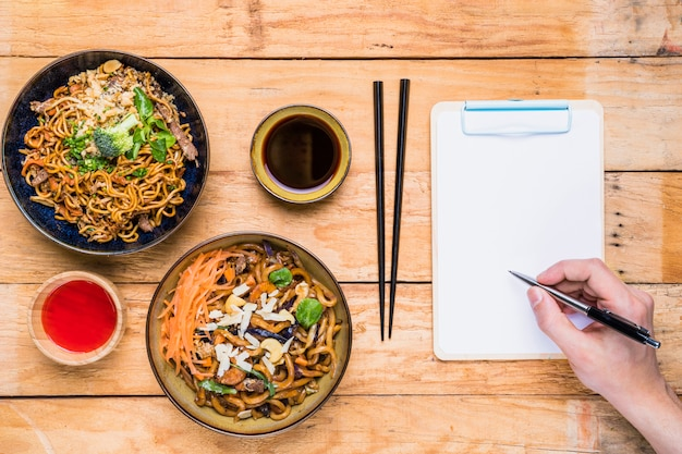 Gros plan, personne, écriture, presse-papiers, stylo, près, thaï, traditionnel, nourriture, sauces, table