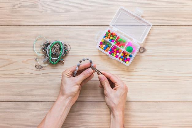 Gros plan, personne, fabrication, fait main, bracelet, pincettes