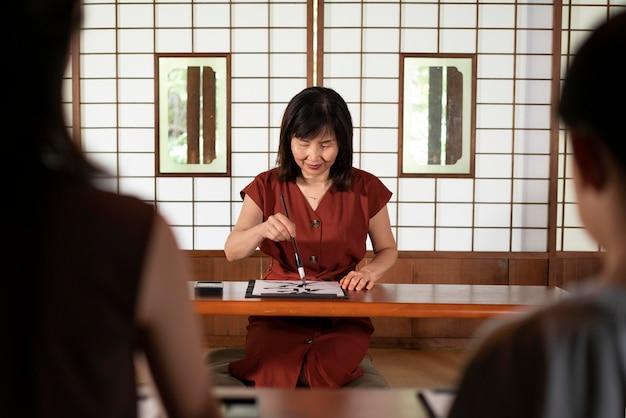 Gros plan sur une personne faisant de la calligraphie japonaise, appelée shodo