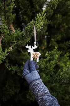 Gros plan personne avec des gants tenant une décoration en forme de renne
