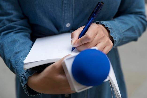 Gros plan sur la personne interrogée prenant des notes