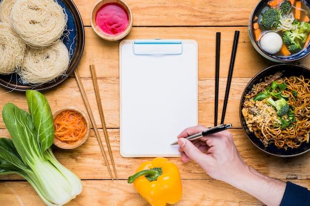 Gros plan, de, personne, main, écriture, sur, presse-papiers, à, cuisine thaï traditionnelle, sur, table en bois