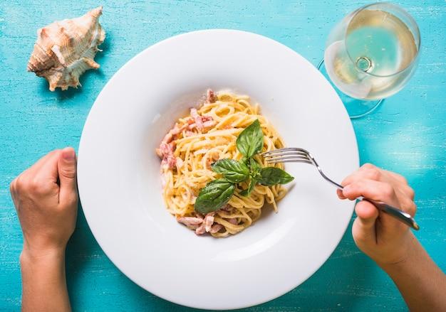 Gros plan, personne, manger, spaghetti, à, verre vin, et, conque, sur, turquoise, toile de fond