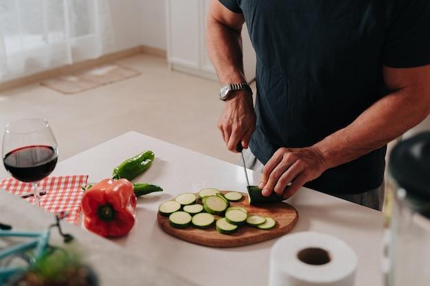Gros plan d'une personne méconnaissable coupant des légumes pour faire de la nourriture