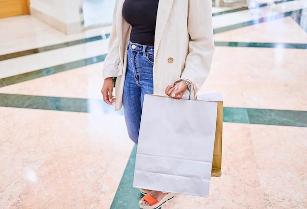 Gros plan d'une personne méconnaissable faisant du shopping avec des sacs