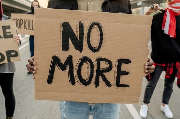 Gros plan sur une personne méconnaissable tenant benner avec plus de mots tout en participant à une émeute