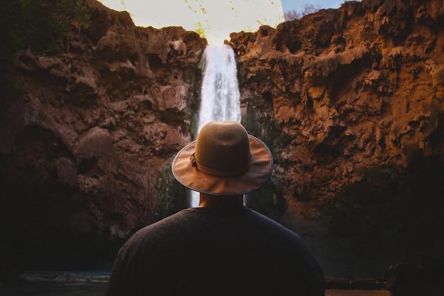 Gros plan d'une personne portant un chapeau brun face à une cascade qui descend les collines