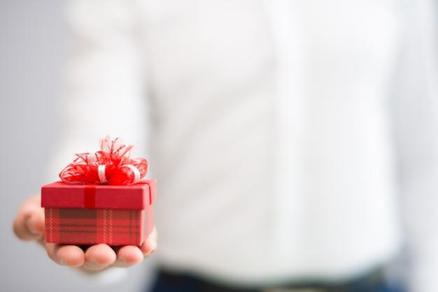 Gros plan d'une personne qui donne une petite boîte cadeau rouge avec un arc