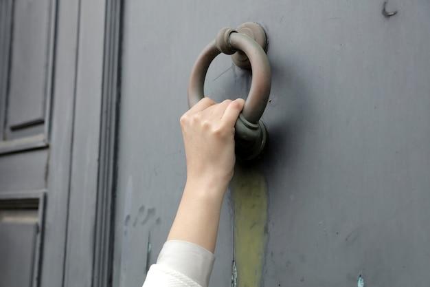 Gros plan d'une personne qui frappe à la porte avec un vieux heurtoir de porte