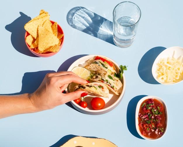 Gros plan personne avec taco et sauce délicieuse