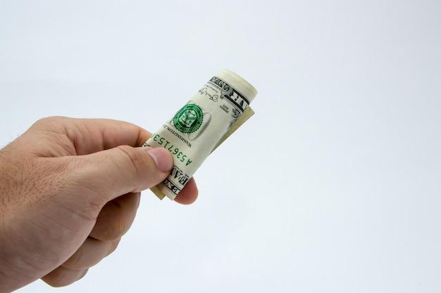 Gros plan d'une personne tenant un billet d'un dollar sur un fond blanc