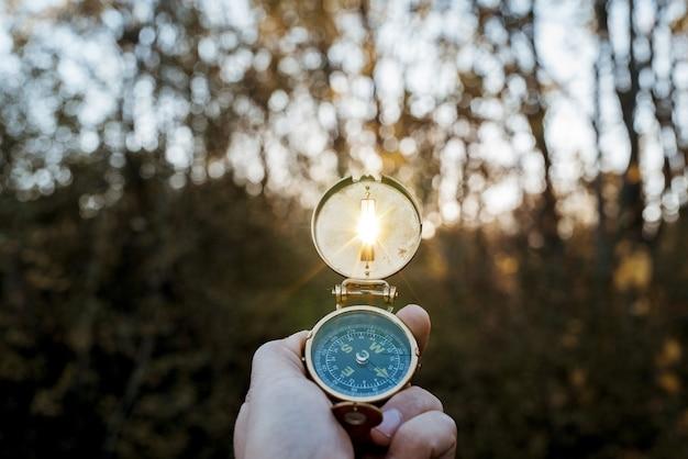 Gros plan d'une personne tenant une boussole avec le soleil qui brille à travers le trou