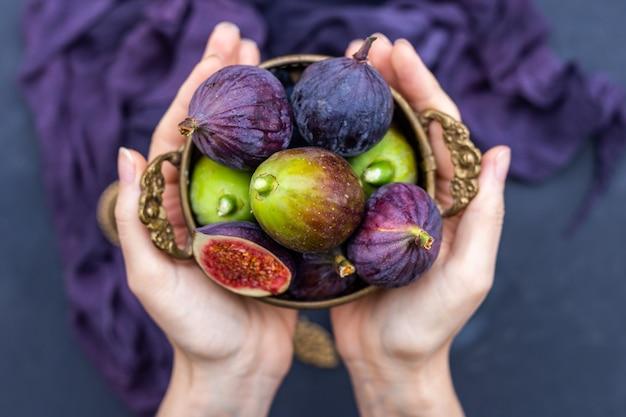 Gros plan d'une personne tenant des figues fraîches