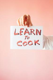 Un gros plan d'une personne tenant un papier avec le mot «apprendre à cuisiner» sur fond rose
