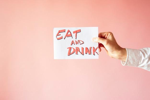 Un gros plan d'une personne tenant un papier avec le mot «manger et boire» sur un mur rose