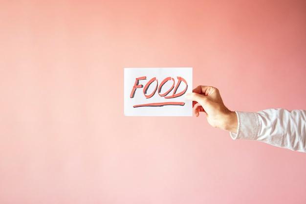 Un gros plan d'une personne tenant un papier avec le mot «nourriture» sur un mur rose