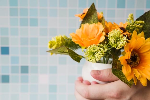 Gros plan, personne, tenue, vase de fleur, main, contre, mosaïque