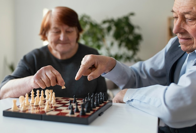Gros plan des personnes âgées jouant aux échecs à l'intérieur