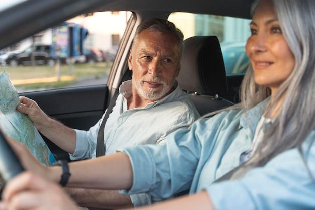 Gros plan des personnes âgées souriantes en voiture