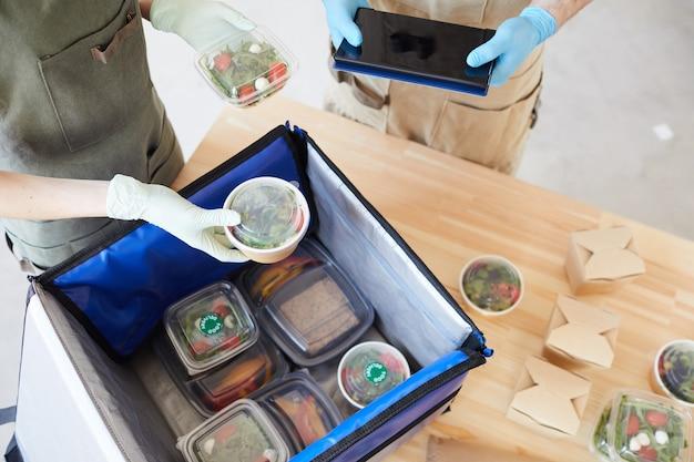 Gros plan de personnes dans des gants de protection d'emballage d'aliments biologiques sains dans un sac pour la livraison