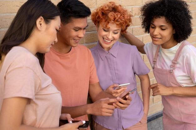 Gros plan des personnes souriantes regardant le téléphone