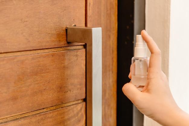 Gros plan sur des personnes utilisant un spray désinfectant à l'alcool pour nettoyer la poignée de porte pour empêcher la propagation de virus ou de germes lors du toucher.