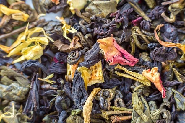 Gros plan des pétales de fines herbes de thé sec abstrait coloré foncé. mode de vie sain, boisson antioxydante naturelle, concept d'aromathérapie.