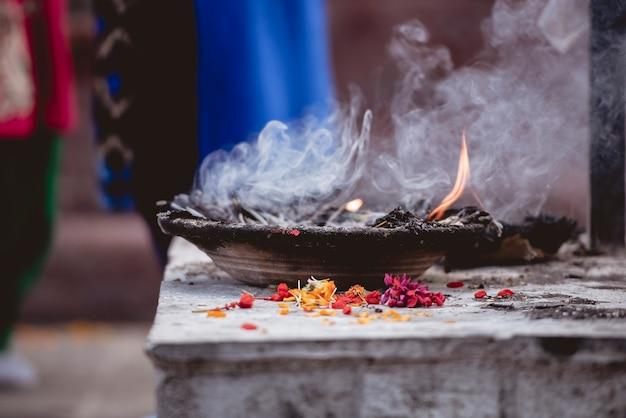Un gros plan de pétales de fleurs brûlant dans un bol en métal pour une cérémonie