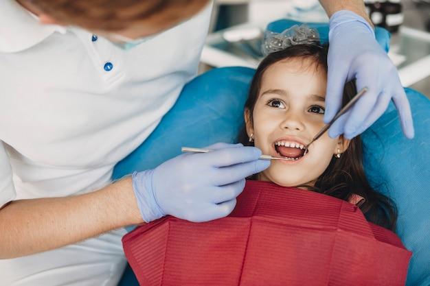 Gros plan d'un petit enfant mignon faisant la chirurgie des dents par un dentiste pédiatrique.