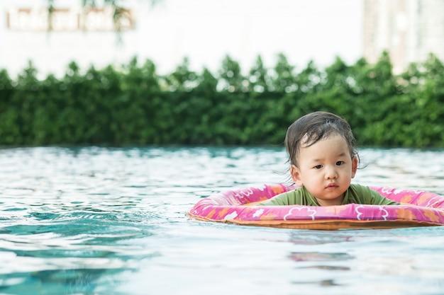 Gros plan d'un petit garçon assis dans un bateau pour les enfants dans la piscine