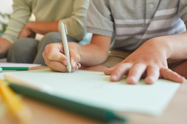 Gros plan d'un petit garçon méconnaissable qui écrit ou dessine pendant la classe de développement, se concentrer sur la main tenant le stylo, copiez l'espace