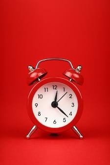 Gros plan sur un petit réveil rétro à double cloche en métal rouge sur fond de papier rouge avec espace de copie, vue de face à faible angle
