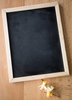Gros plan d'un petit tableau noir allongé sur une table avec des fleurs séchées