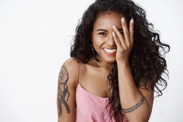 Gros plan petite amie joyeuse et joyeuse avec des tatouages et un sourire blanc à pleines dents, riant, couvrant la moitié du visage, regardant la caméra optimiste, profitant de la fête avec une compagnie amicale, s'amusant