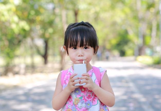 Gros plan de petite fille, boire du lait avec de la paille dans le parc. portrait en plein air