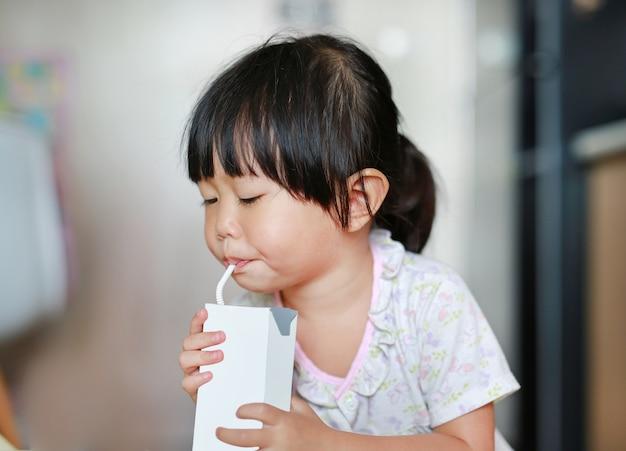 Gros plan de petite fille, boire du lait avec de la paille.