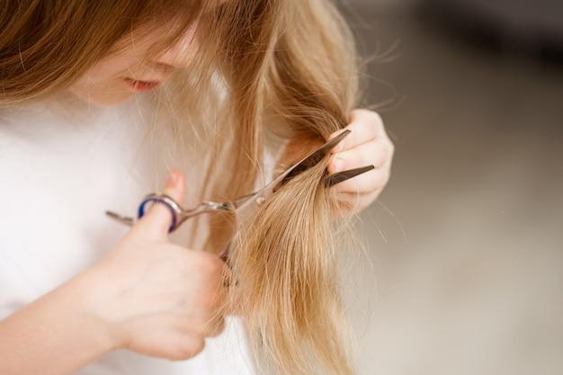 Gros plan la petite fille cisaille ses longs cheveux avec des ciseaux sur blanc