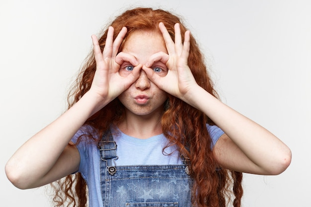 Gros plan d'une petite fille drôle et joyeuse avec des cheveux roux et des taches de rousseur, regarde à travers les mains, a l'air mignon, se dresse sur fond blanc.