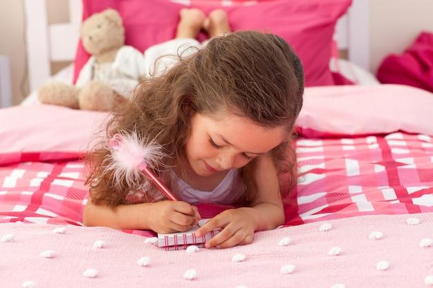 Gros plan d'une petite fille écrivant sur le lit