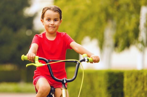 Gros plan, petite fille, face, vélo, regarder appareil-photo, et, sourire