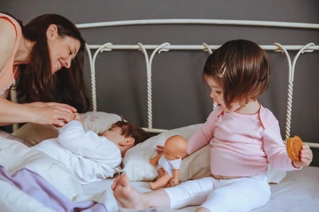 Gros plan d'une petite fille heureuse tenant une poupée et un biscuit pendant qu'une femme joue avec un garçon au-dessus du lit. concept de temps libre en famille le week-end.