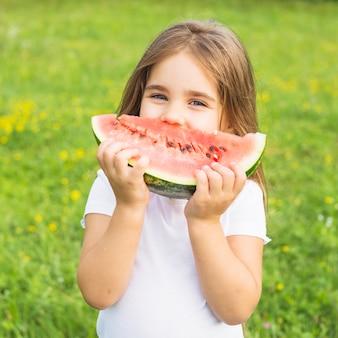 Gros plan, de, petite fille, manger, pastèque, debout, dans parc