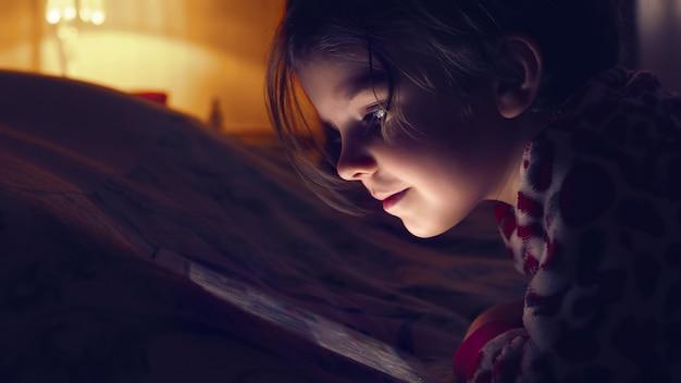 Gros plan d'une petite fille mignonne dans l'obscurité totale en regardant la tablette