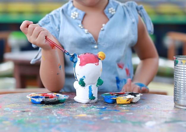 Gros plan petite fille peindre sur une poupée en stuc.