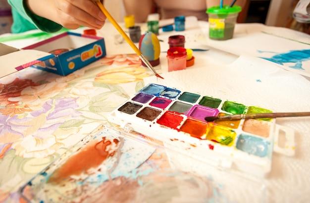 Gros plan d'une petite fille tenant un pinceau et prenant de l'aquarelle