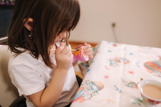 Gros plan de petite fille tenir l'oeuf de pâques dans la main et faire une photo