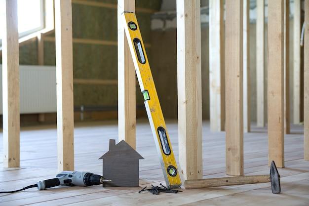 Gros plan d'une petite maison modèle brune et des outils de construction sur des planches de bois dans une pièce inachevée sous fond de construction. investissements dans l'immobilier, la propriété et la propriété du concept de maison de rêve.