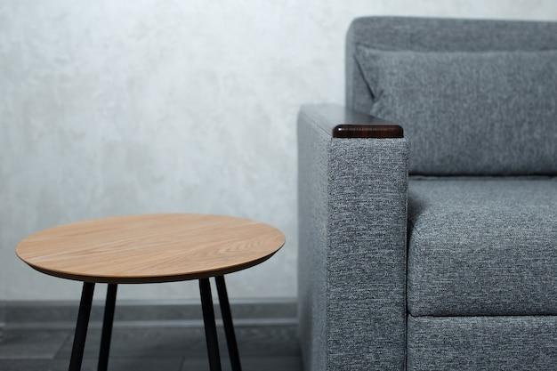 Gros plan d'une petite table ronde en bois près d'un canapé gris sur fond de mur texturé.