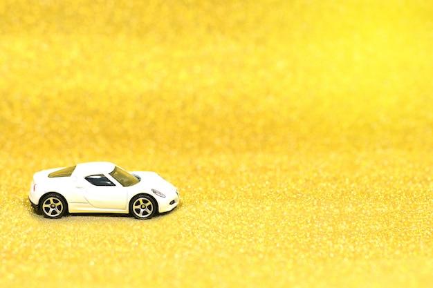 Gros plan d'une petite voiture sur fond de paillettes avec copie espace